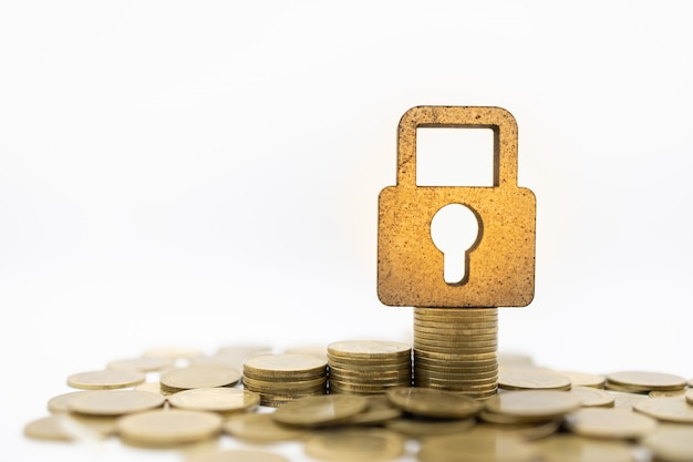 Wooden master key lock icon on top of stack of gold coins on white.
