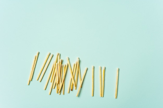 Wooden matches scattered on a turquoise pastel color background