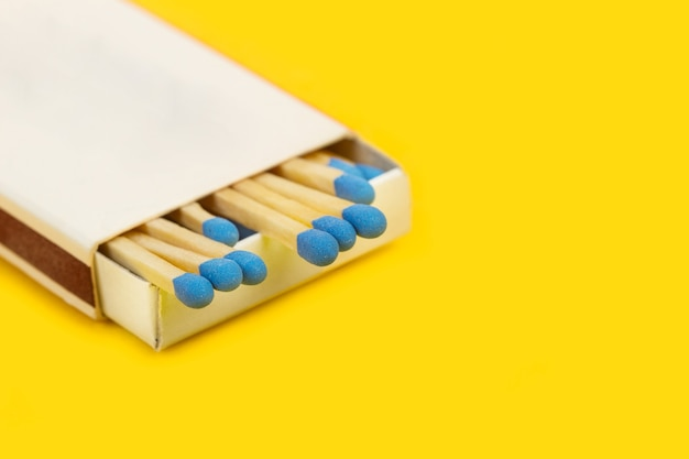 Wooden matches sticks with blue head in a match box isaolated