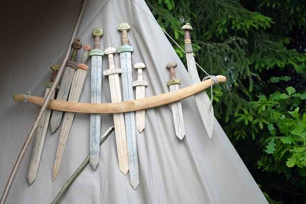Wooden medieval weapons replicas for close combat displayed on a tent.