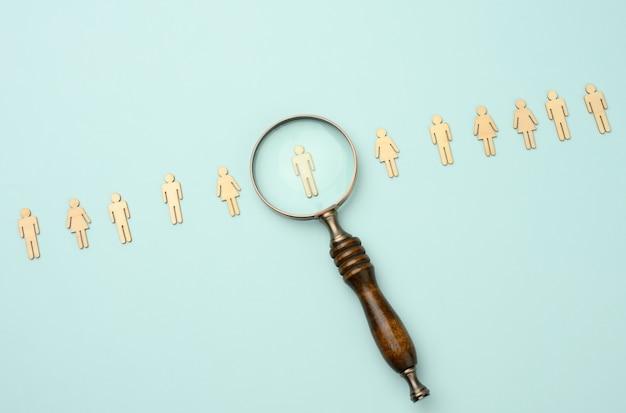 나무 남자와 파란색 배경에 돋보기. 채용 개념, 재능 있고 유능한 직원 검색, 경력 성장, 평평한 평신도