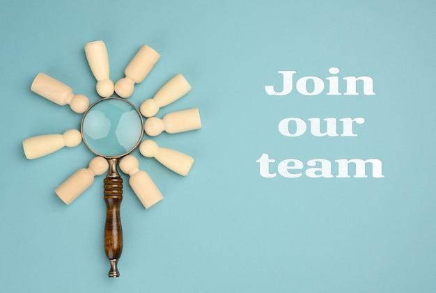 Деревянные человечки и увеличительное стекло на синем фоне. концепция подбора персонала, поиск талантливых и способных сотрудников, карьерный рост. присоединиться к нашей команде