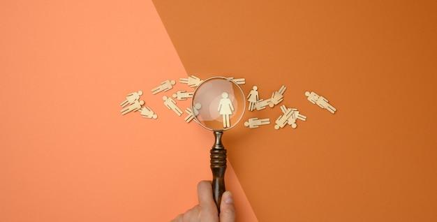 Деревянные человечки и увеличительное стекло на коричневом фоне. концепция подбора персонала, поиск талантливых и способных сотрудников, карьерный рост, плоская планировка