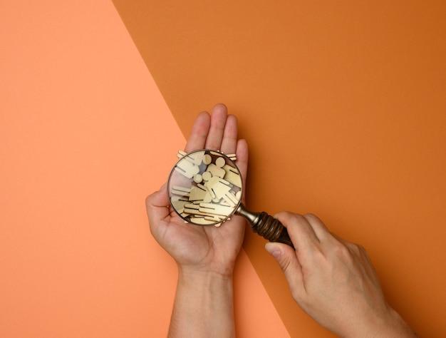 Деревянные человечки и увеличительное стекло на коричневом фоне. концепция подбора персонала, поиск талантливых и способных сотрудников, карьерный рост
