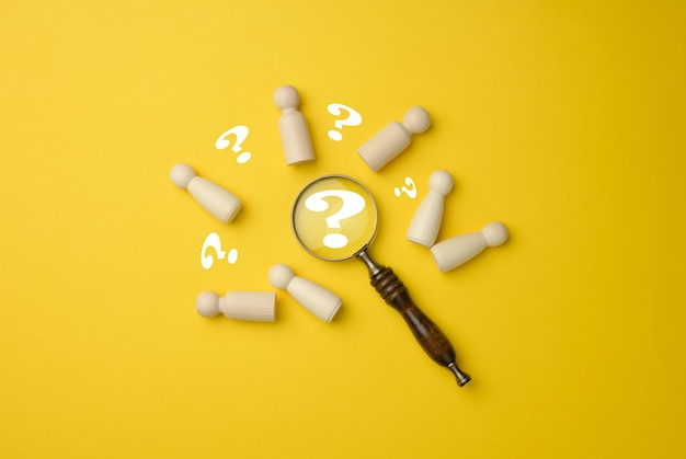 Деревянные человечки и увеличительное стекло на желтом фоне. концепция подбора персонала, поиск талантливых и способных сотрудников, карьерный рост, плоская планировка