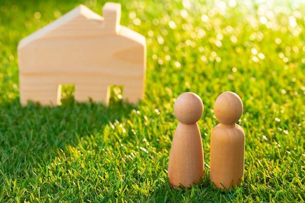 나무 남자 인물 및 장난감 목조 주택 가까이