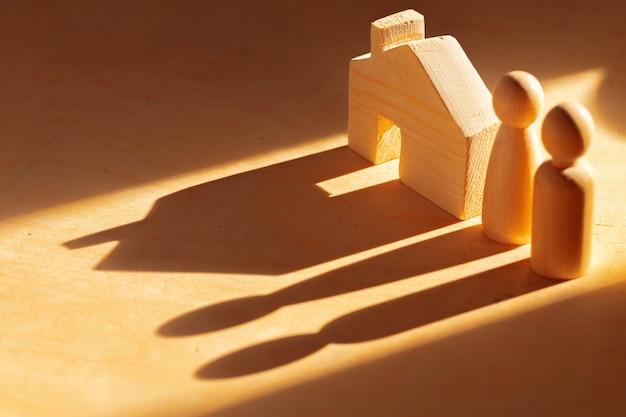 Деревянные мужские фигуры и игрушечный деревянный дом крупным планом