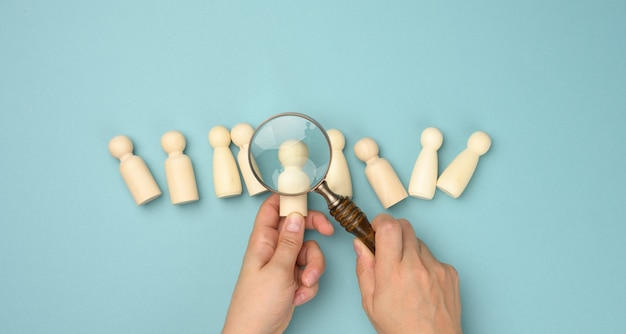 Wooden men and a magnifying glass on a blue background. recruitment concept, search for talented and capable employees, career growth, flat lay