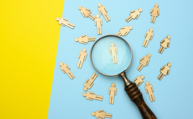 Wooden men and a magnifying glass on a blue background. recruitment concept,