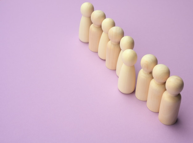 Wooden men stand in a row, one figurine sticking out in front. the concept of exclusivity, talent