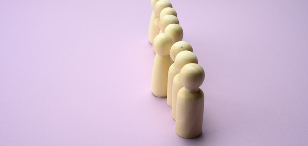 Wooden men stand in a row, one figurine sticking out in front