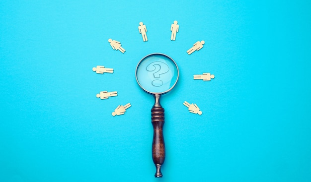Wooden men and vintage magnifying glass on a blue background recruitment, search for talented employees, who is next, flat lay