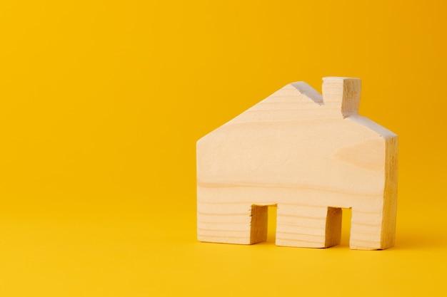 黄色の背景に木製のミニ家モデルをクローズアップ