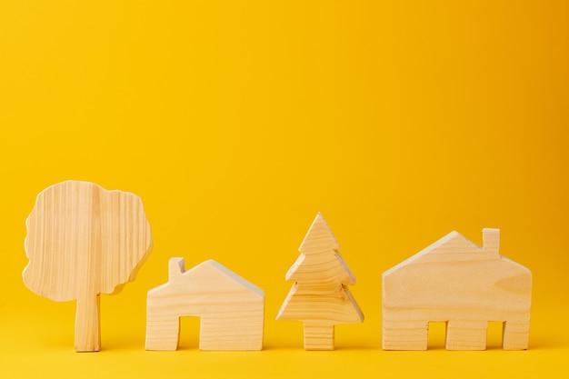 黄色の背景に木製のミニ家モデル