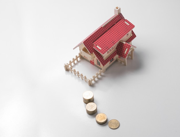 Wooden model house with money on white table