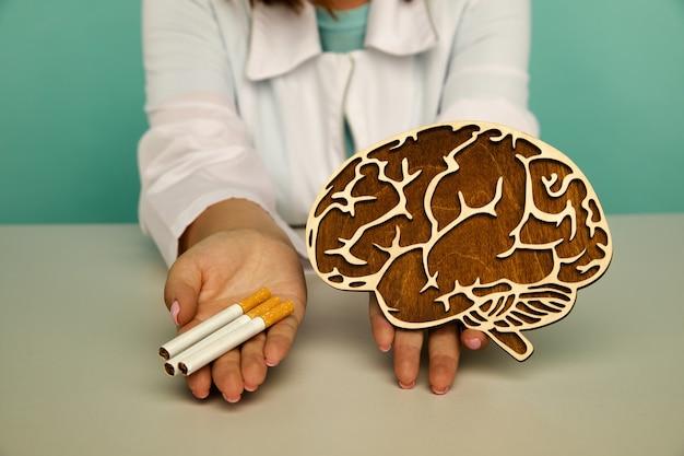 中毒を吸う看護師の手に脳とタバコの木製モデル