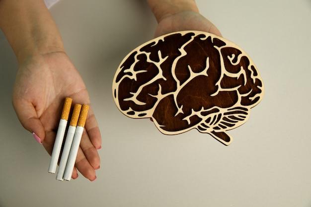 看護師の上面図の手に脳とタバコの木製モデル