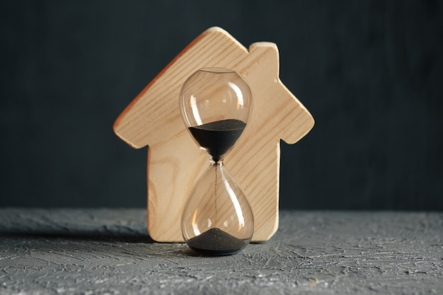 Деревянная модель дома и крупным планом песочные часы. сохранение и покупка концепции недвижимости. Premium Фотографии