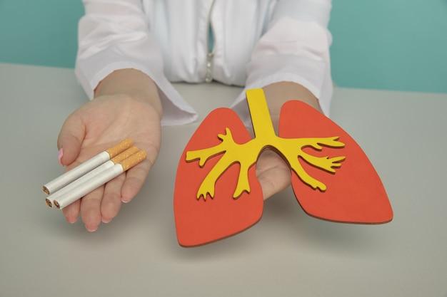 中毒を喫煙している看護師の手にある肺とタバコの木製モデル