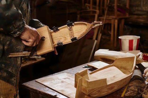Деревянные модели кораблей на столе плотника на фоне работающего мастера. мастер фиксирует древесный материал струбциной.