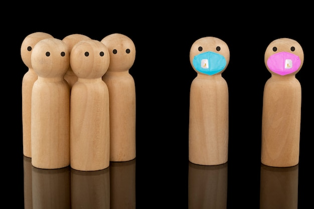 Деревянные модели стоят отдельно и в синих и розовых масках для лица, некоторые модели стоят в группе и ничего не одеты. концепции ношения маски социального дистанцирования.