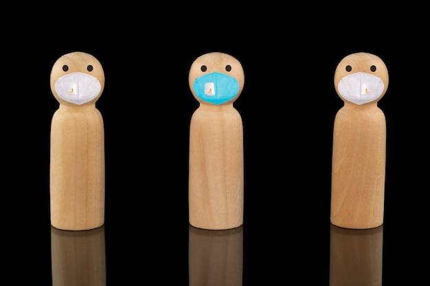 파란색과 흰색 얼굴 마스크를 쓴 나무 모델. 사회적 거리 개념.