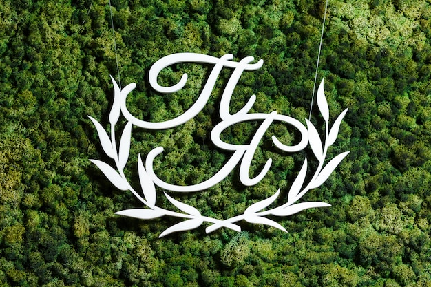 Wooden monogram white initials of the newlyweds on the background of green moss wedding decor