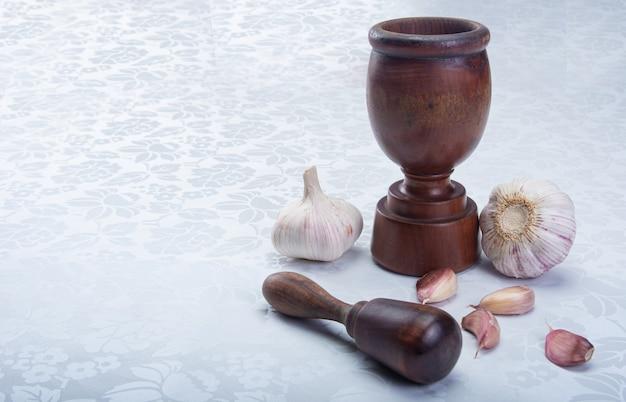 白いタオルの上に木製の乳鉢とニンニク。
