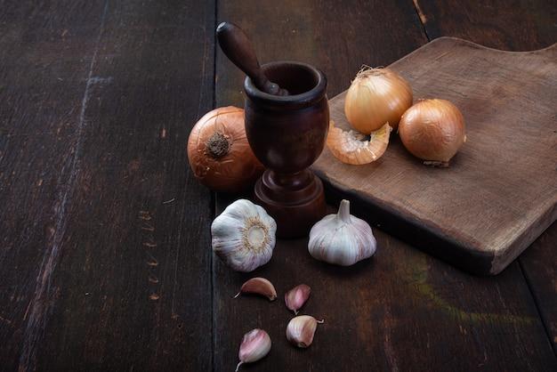 木の上に素朴な配置の木製の乳鉢とスパイス。