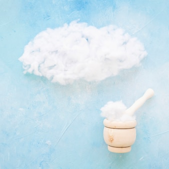 Wooden mortar and pestle with cloud on blue background
