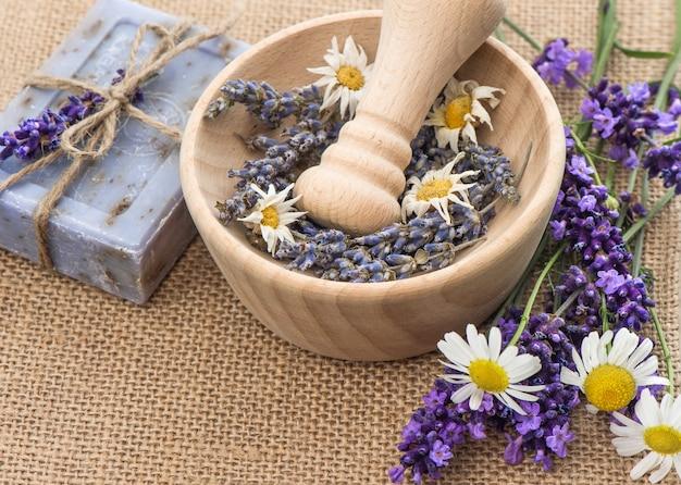 Деревянная ступка со свежими цветами лаванды и ромашки. выборочный фокус