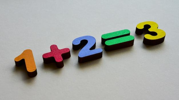 Деревянные разноцветные цифры иллюстрируют функцию сложения на бежевом фоне. вид сбоку. элементарная математика, детский день.
