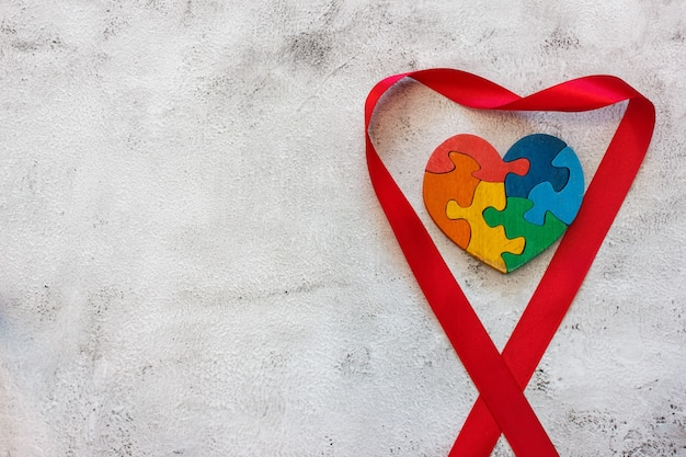 Wooden multicolor puzzle in the form of heart on gray background. concept valentines day, relationship. space for text