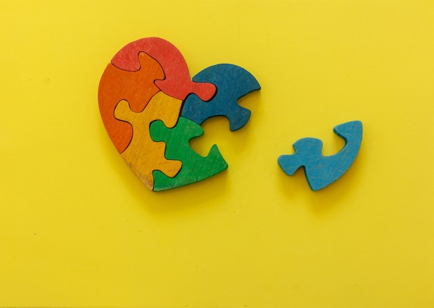 Wooden multicolor puzzle in the form of heart on yellow background. concept valentines day, relationship. space for text