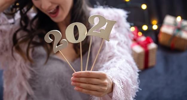 女の子の手に木製の新年の数がクローズアップ。