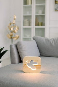 Wooden night lamp with bee picture, on gray monochrome sofa, at stylish light home living room interior