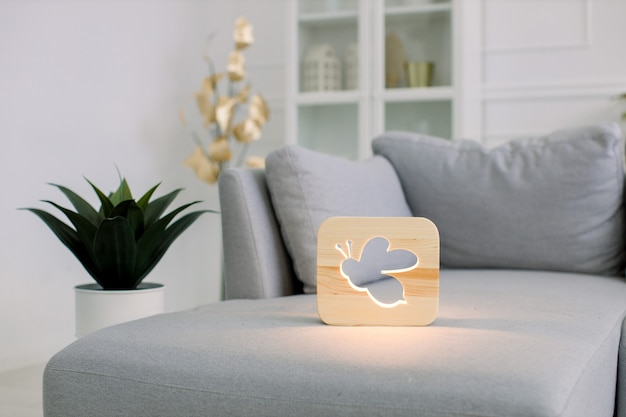 Wooden night lamp with bee picture, lying on gray modern sofa, at stylish light home living room interior.