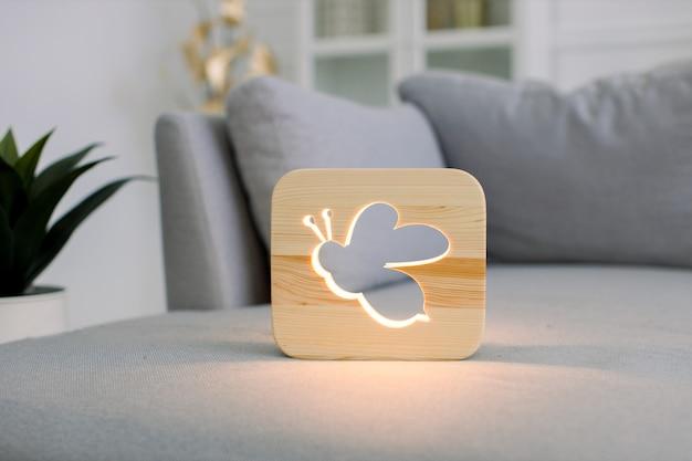 Деревянный ночник с изображением пчелы на сером монохромном диване в стильном светлом домашнем интерьере гостиной