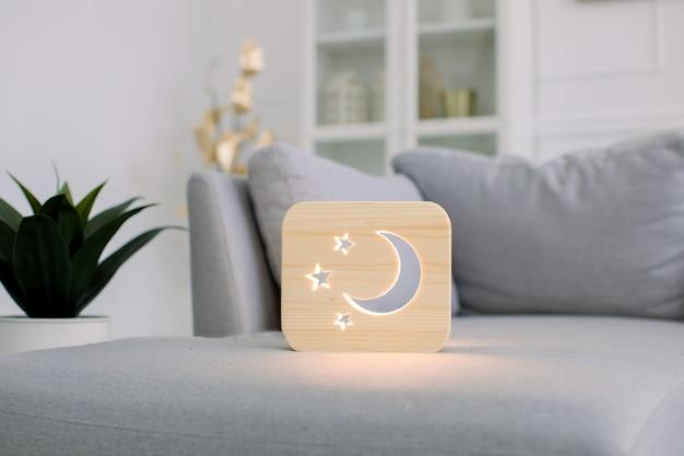 Деревянный ночник с изображением луны и звезд на сером диване в стильном светлом домашнем интерьере гостиной