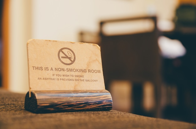 Wooden non smoking sign on sofa in room