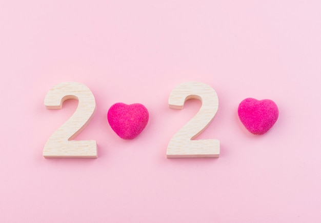 Wooden number of 2020 with pink heart on pink background