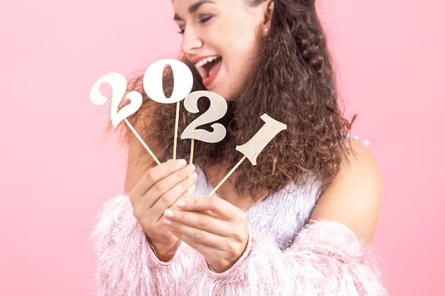 Деревянный номер для новогодней концепции в руках красивой веселой девушки на розовом студийном фоне
