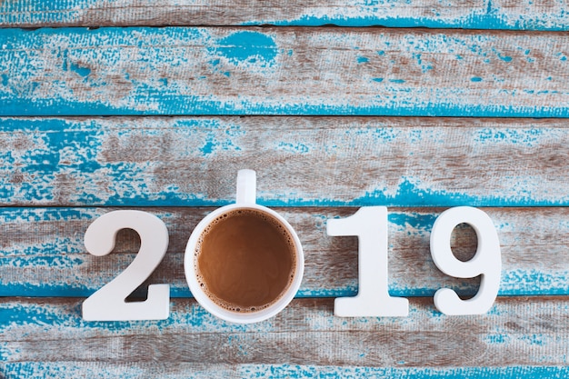 Wooden number and hot coffee with 2019 text on rustic blue wooden table