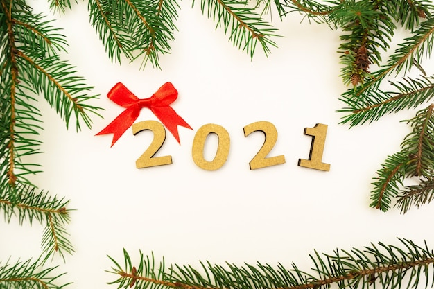 Wooden numbers 2021 and green spruce branches on a white background.