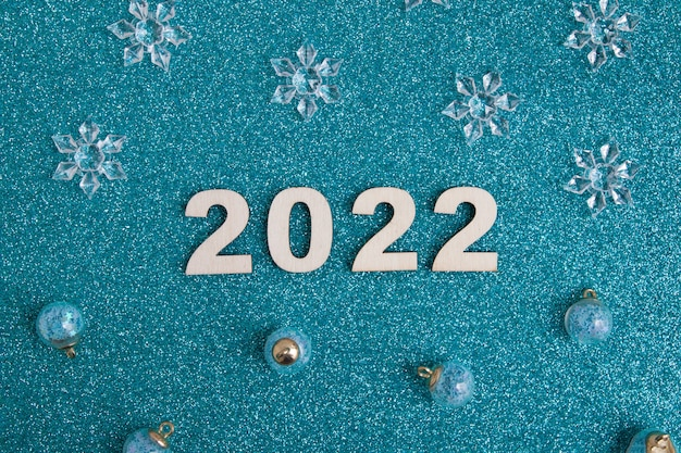 Wooden numbers new year 2022 with christmas decor on glitter blue background