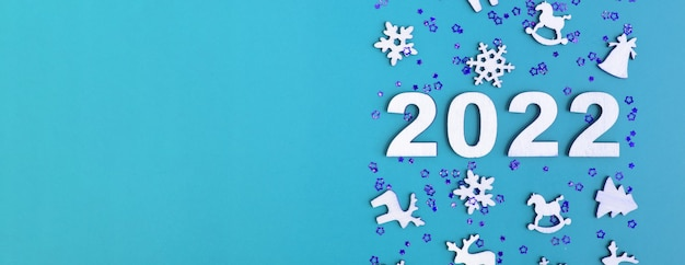 Wooden numbers for new year 2022 with stars and christmas decor on blue background with copy space. banner format