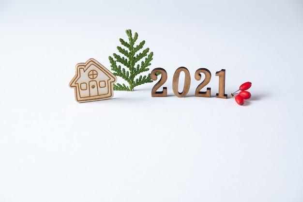 木製の数字と近くの小さな家。ミニマリズムとコピースペース。家にいるコンセプト。