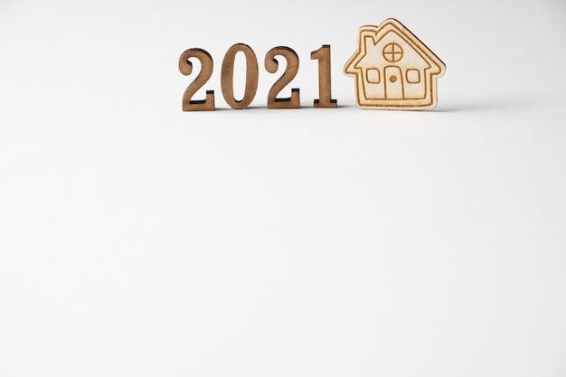 木製の数字と近くの小さな家。ミニマリズムとコピースペース。