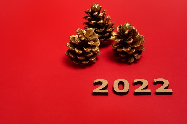 Wooden numerals lying down on red colored background next to christmas pine cones paints in golden color, with copy space for new year advertising. celebration, event, holidays concept