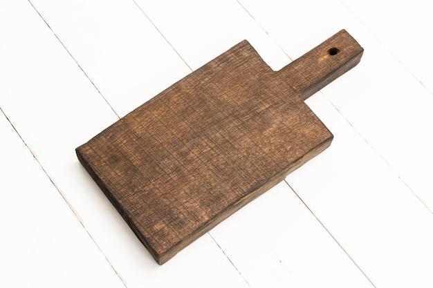 白い木製のテーブルの上の木製オークまな板